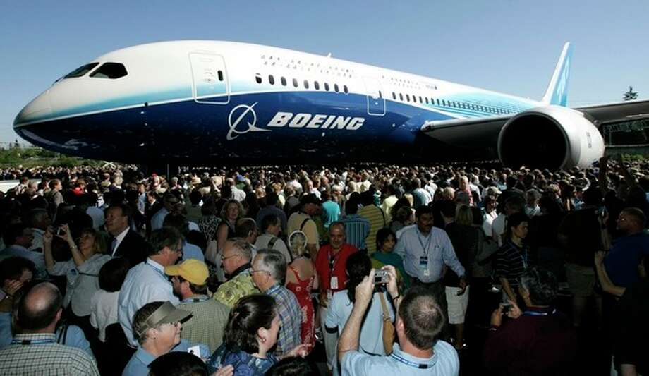 FILE - In this July 8, 2007, file photo, visitors look at and take photos of the first production model of the new Boeing 787 airplane after it was unveiled to an audience of several thousand at Boeing's assembly plant in Everett, Wash. The Boeing 787 was a plane that promised to be lighter and more technologically advanced than any other, but once production started, the gap between vision and reality quickly widened. The jet that was eventually dubbed the Dreamliner became plagued with manufacturing delays, cost overruns and sinking worker morale. (AP Photo/Ted S. Warren, File) / AP