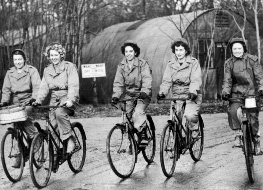 FILE - In this Dec. 22, 1943, file photo, members of the Women Army Corps (WAC) stationed at a U.S. medium bomber station in England, ride bicycles on their way to work. (AP Photo, File) / AP