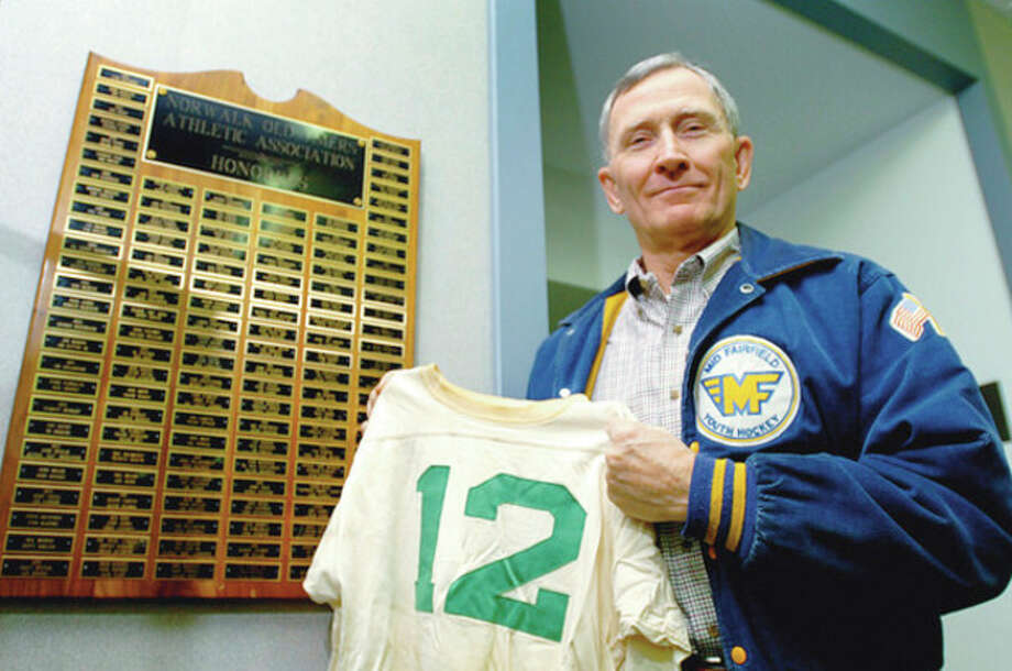 Hour photo/ERIK TRAUTMANN Dennis D'Amato holds his old Norwalk High School football jersey while standing beside the Norwalk Old Timers Honor Roll in the lobby at City Hall, which was once his high school. D'Amato, a 2004 Norwalk Old Timers honoree, recently became president of the local organization. / (C)2011, The Hour Newspapers, all rights reserved