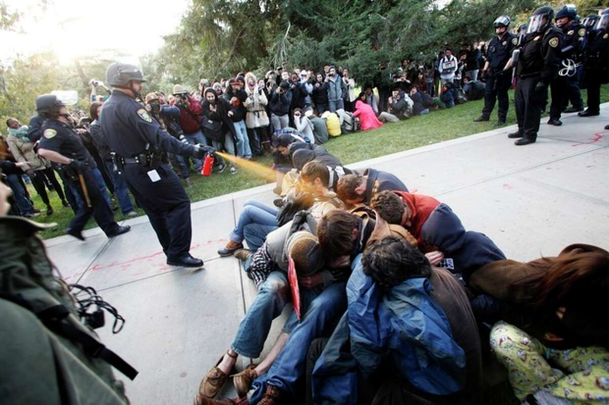 FILE - In this Nov. 18, 2011 file photo, University of California, Davis Police Lt. John Pike uses pepper spray to move Occupy UC Davis protesters while blocking their exit from the school's quad in Davis, Calif. Most major Occupy Wall Street encampments in the U.S. have been dispersed, but they live on in a flurry of lawsuits in which protesters are asserting their constitutional rights to free speech and assembly and challenging authorities' use of force to break up tent cities. (AP Photo/The Enterprise, Wayne Tilcock, File)
