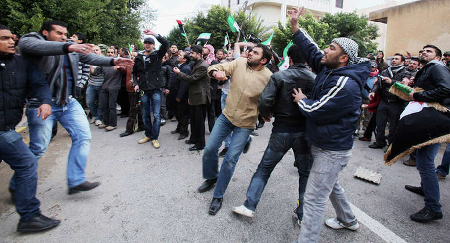 Men chant slogans during an anti-Syrian regime protest in front of the Chinese embassy in Tripoli, Libya, Monday, Feb. 6, 2012. Russia and China have vetoed a U.N. Security Council resolution aimed at ending Syria's bloodshed, despite international outrage over a devastating bombardment of the city of Homs by President Bashar Assad's forces. The veto and the show of support by Russia last Saturday raised concerns that Assad's regime could now unleash even greater violence to crush the revolt against his rule, assured that his ally would prevent international action while continuing its weapons sales to Damascus. (AP Photo/Abdel Magid al-Fergany) / AP