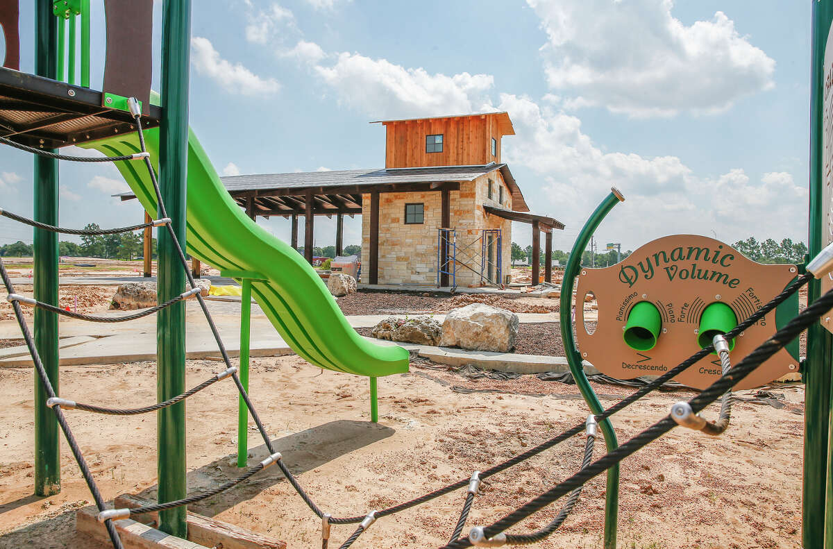 A pavillion with restrooms and playground equipment rises from the soil at the 32-acre park under construction next to Cinco Ranch High School.