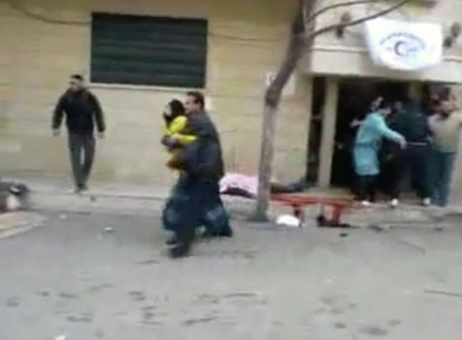 This image from amateur video made available by Shaam News Network on Monday, Feb. 6, 2012, purports to show people outside a hospital in Homs, Syria. Government forces shelled the central Syrian city of Homs on Monday, striking a makeshift medical clinic and residential areas and killing more than a dozen people in the third day of a new assault on the epicenter of the country's uprising, activists said. (AP Photo/Shaam News Network via APTN) THE ASSOCIATED PRESS CANNOT INDEPENDENTLY VERIFY THE CONTENT, DATE, LOCATION OR AUTHENTICITY OF THIS MATERIAL. TV OUT / Shaam News Network
