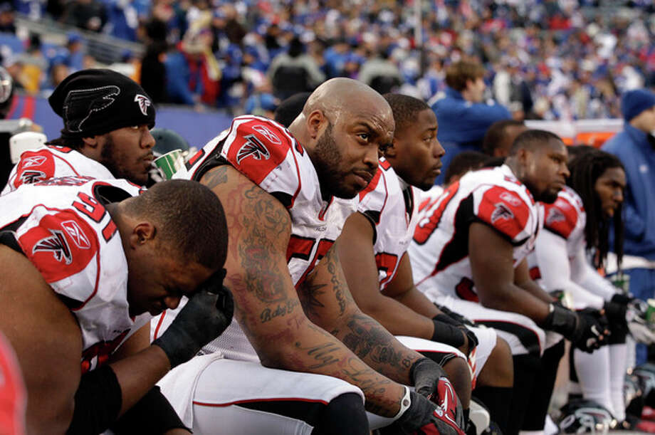 Atlanta Falcons defensive end John Abraham, third left, sits on the bench with his teammates during the second half of an NFL wild card playoff football game against the New York Giants Sunday, Jan. 8, 2012, in East Rutherford, N.J. The Falcons lost the game 24-2. (AP Photo/Matt Slocum) / AP