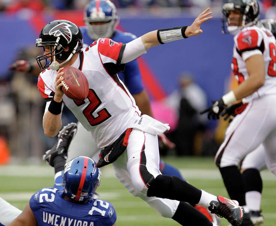 Atlanta Falcons quarterback Matt Ryan (2) runs over New York Giants defensive end Osi Umenyiora (72) during the first half of an NFL wild card playoff football game Sunday, Jan. 8, 2012, in East Rutherford, N.J. (AP Photo/Julio Cortez) / AP