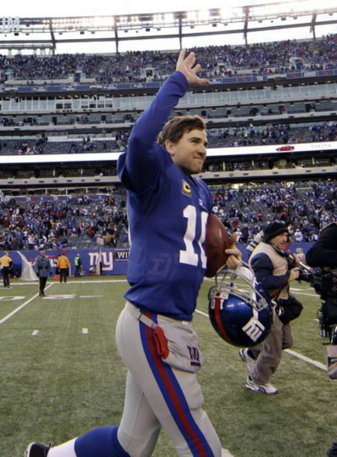New York Giants quarterback Eli Manning waves to spectators after an NFL wild card playoff football game against the Atlanta Falcons Sunday, Jan. 8, 2012, in East Rutherford, N.J. The Giants defeated the Falcons 24-2. (AP Photo/Matt Slocum)