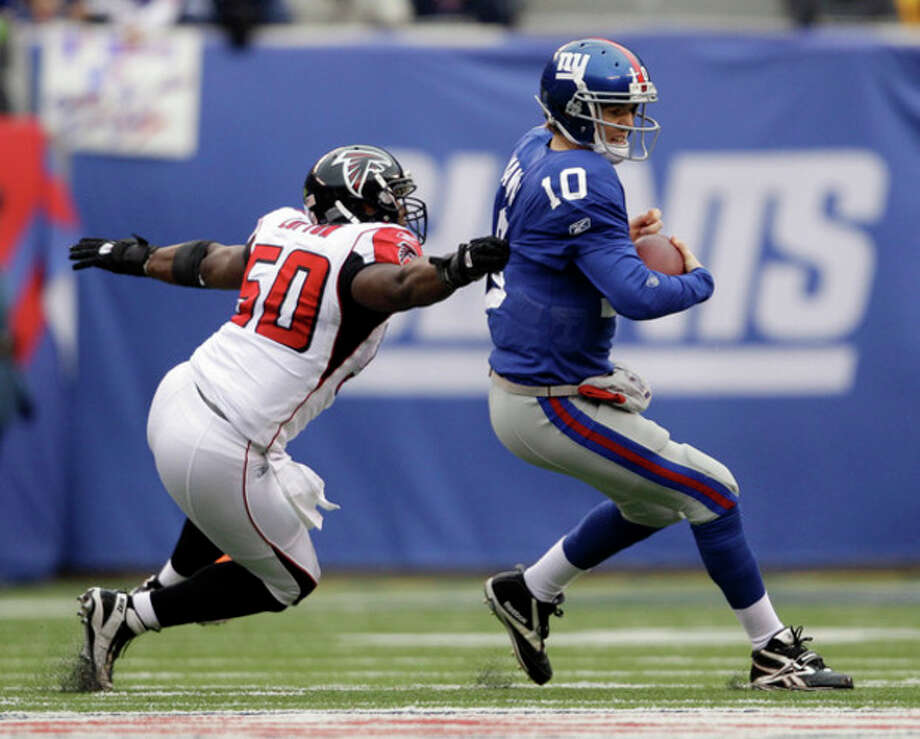New York Giants quarterback Eli Manning (10) evades a tackle by Atlanta Falcons middle linebacker Curtis Lofton (50) during the first half of an NFL wild card playoff football game Sunday, Jan. 8, 2012, in East Rutherford, N.J. (AP Photo/Matt Slocum) / AP