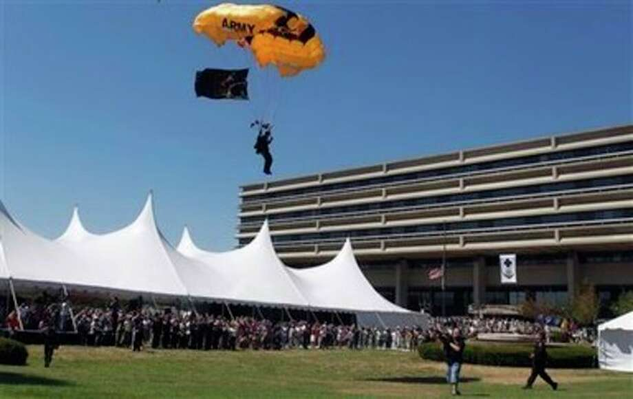 A member of the U.S. Army Golden Knights parachutes onto the front lawn of the Walter Reed Army Medical Center in Washington, Wednesday, July 27, 2011, after a flag casing ceremony. Walter Reed Army Medical Center, the military's flagship hospital where privates to presidents have gone for care for more than a century, is closing its doors.(AP Photo/Luis M. Alvarez) / FR596 AP