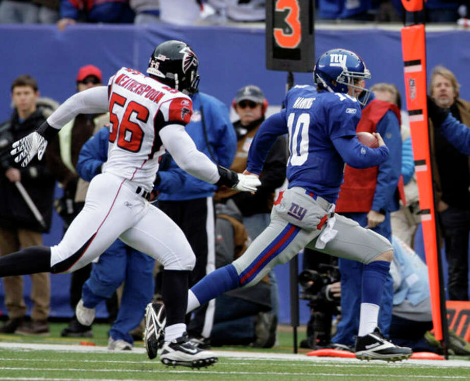 New York Giants quarterback Eli Manning (10) is chased by Atlanta Falcons outside linebacker Sean Weatherspoon (56) during the first half of an NFL wild card playoff football game Sunday, Jan. 8, 2012, in East Rutherford, N.J. (AP Photo/Peter Morgan) / AP