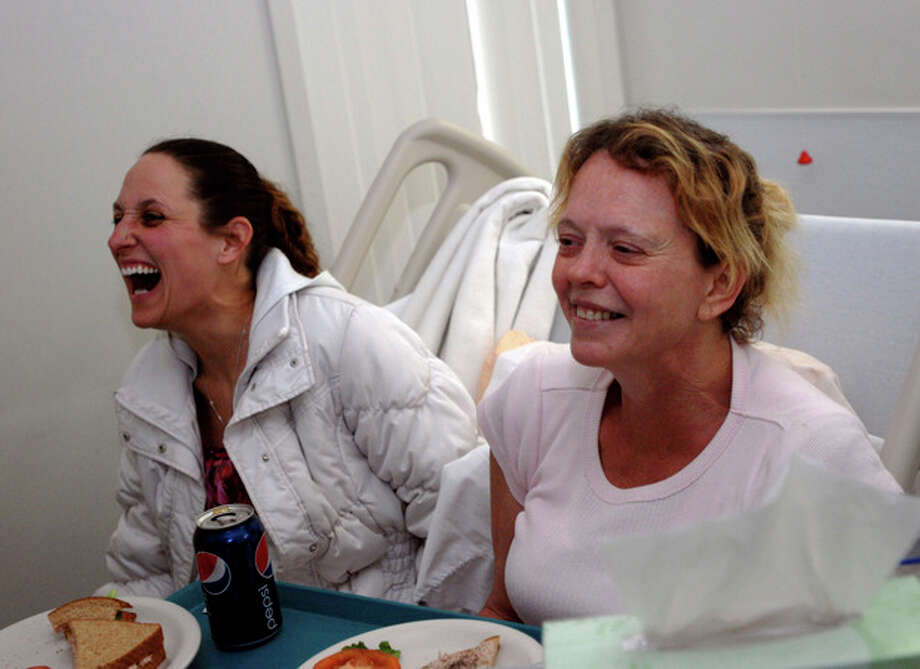 Belinda Conne, right, shares a laugh with an unidentified friend Sunday, Feb. 5, 2012 in her hospital bed in Gold Beach, Ore. Conne, her husband, Dan, and son, Michael were rescued Saturday after spending six nights lost in the woods with their dog. (AP Photos/Jeff Barnard) / AP2012