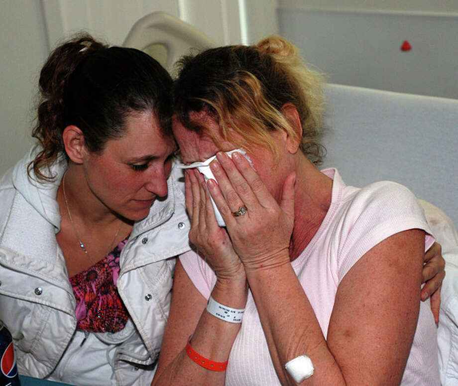 Belinda Conne, right, cries in the arms of a friend Sunday, Feb. 5, 2012 at a hospital in Gold Beach, Ore., at the thought she and her husband and son might have killed their dog for food if they hadn't been found after six nights lost in the woods. The three were rescued Saturday after a volunteer helicopter pilot spotted them on the edge of a ravine in tall timber. (AP Photo/Jeff Barnard) / AP2012