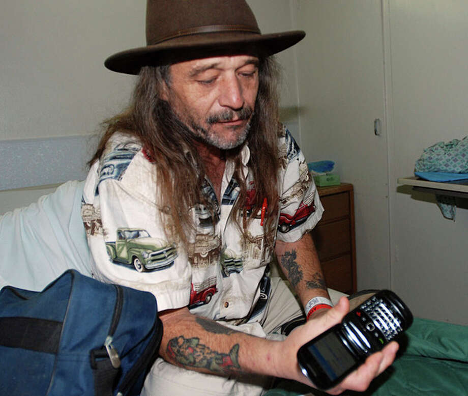 Dan Conne sits in a hospital bed in Gold Beach, Ore., on Sunday, Feb. 5, 2012 showing how his wife, Belinda used their dead cellphone and he used a sheath knife to flash a signal to a search helicopter that found them Saturday. The Connes and their son, Michael, spent six nights lost in cold, wet woods before their were found Saturday. (AP Photo/Jeff Barnard) / AP