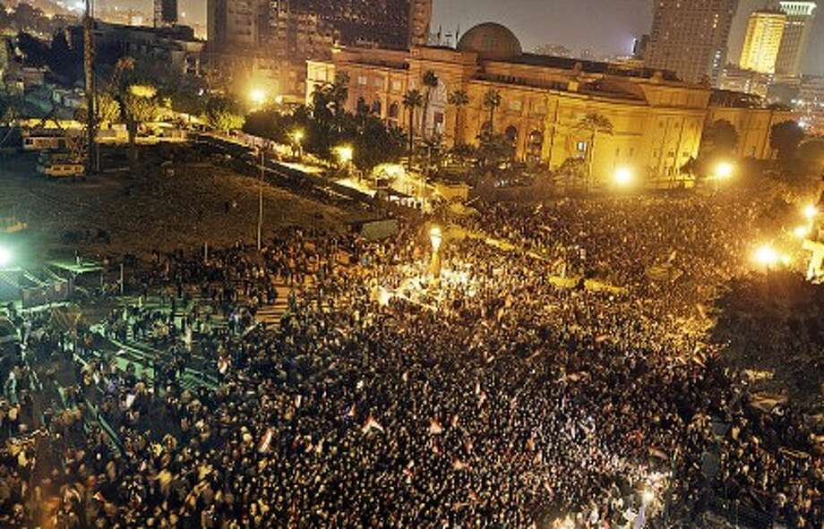 Egyptians celebrate the news of the resignation of President Hosni Mubarak, who handed control of the country to the military, in front of the Egyptian museum at night in Tahrir Square in downtown Cairo, Egypt Friday, Feb. 11, 2011.