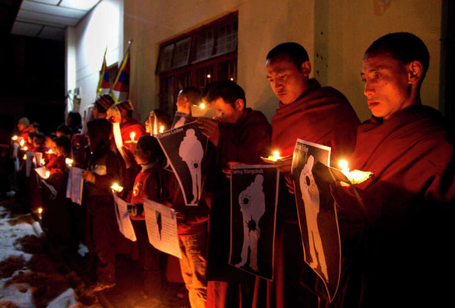 FILE - In this file photo taken Wednesday, Jan. 25, 2012, Tibetan Buddhist monks hold pictures of Tibetans they claim were allegedly shot by Chinese security forces earlier this week, during a candlelight vigil in Dharamsala, India. Three deadly clashes with Chinese security forces in January mark an escalation of a Tibetan protest movement that had expressed itself through scattered individual self-immolations, reflecting both the growing desperation of Tibetans and the harsh response by police. (AP Photo/Angus McDonald, File) / AP