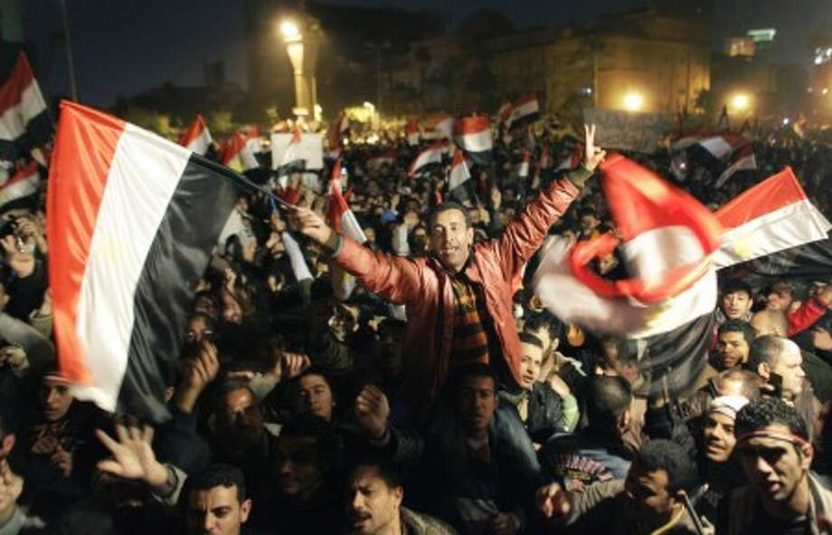 Egyptians celebrate the news of the resignation of President Hosni Mubarak, who handed control of the country to the military, at night in Tahrir Square in downtown Cairo, Egypt Friday, Feb. 11, 2011.