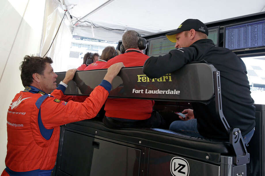 Michael Waltrip, lower left, and co-driver Clint Bowyer, right, talk in their pit stall during practice for the Rolex 24 hour auto race at Daytona International Speedway, Thursday, Jan. 24, 2013, in Daytona Beach, Fla. (AP Photo/John Raoux) / AP