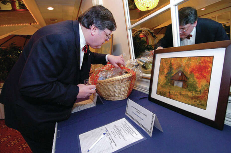 Hour Photo Alex von Kleydorff; Attorney Matt Miklave takes a close look at a gift basket of 'Adult Beverages' of Scotch, Gin and other treats donated by Diago for the Mayors Ball silent auction. / 2013 The Hour Newspapers/Alex von Kleydorff