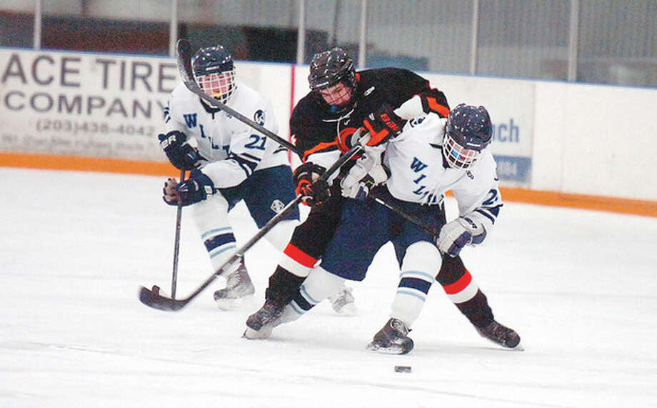 Hour photo/Alex von KleydorffStamford's Matt Savona, center, tries to climb over the back of Wilton's Kyle McCormick as the two pursue the puck during Friday afternoon's game at the Winter Garden Arena in Ridgefield. Stamford skated to a 5-3 victory over the struggling Warriors. / 2013 The Hour Newspapers