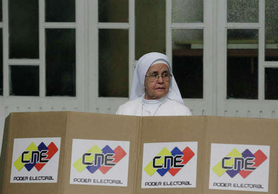 A nun looks up from a voting booth while marking her ballot at a polling station in Caracas, Venezuela, Sunday Feb. 12, 2012. Citizens head to the polls in Venezuela's first-ever opposition primary Sunday to choose a candidate that will challenge President Hugo Chavez in October. (AP Photo/Fernando Llano) / AP