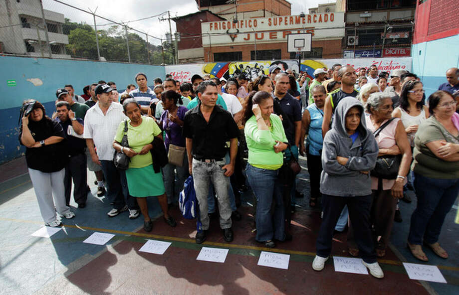 People wait in line to cast their ballots in the opposition primary election in Caracas, Venezuela, Sunday Feb. 12, 2012. Voters head to the polls in Venezuela's first-ever opposition primary Sunday to choose a candidate that will challenge President Hugo Chavez in October. (AP Photo/Ariana Cubillos) / AP