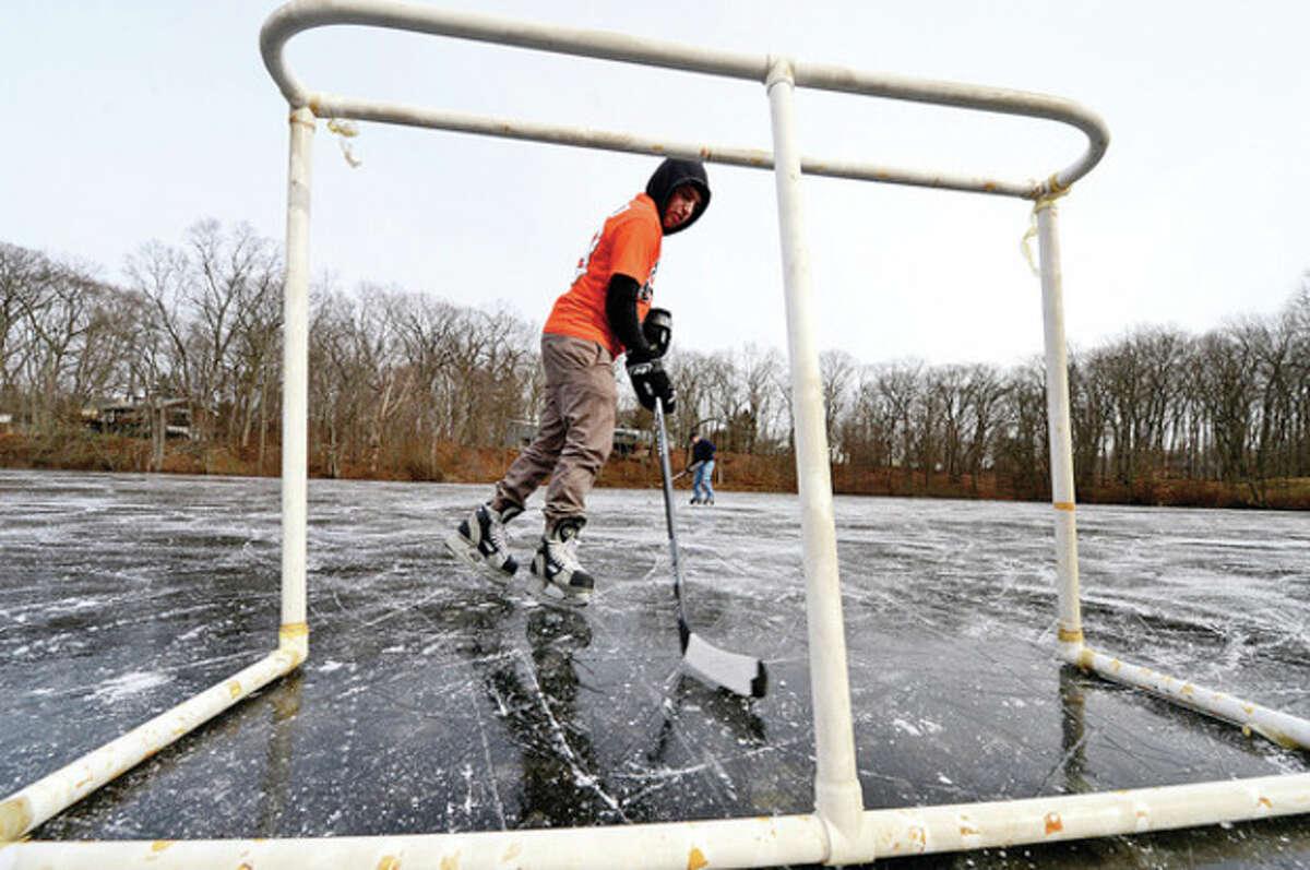 Hour photo / Erik Trautmann Ed Goobic ice skates at Woods Pond Friday afternoon.