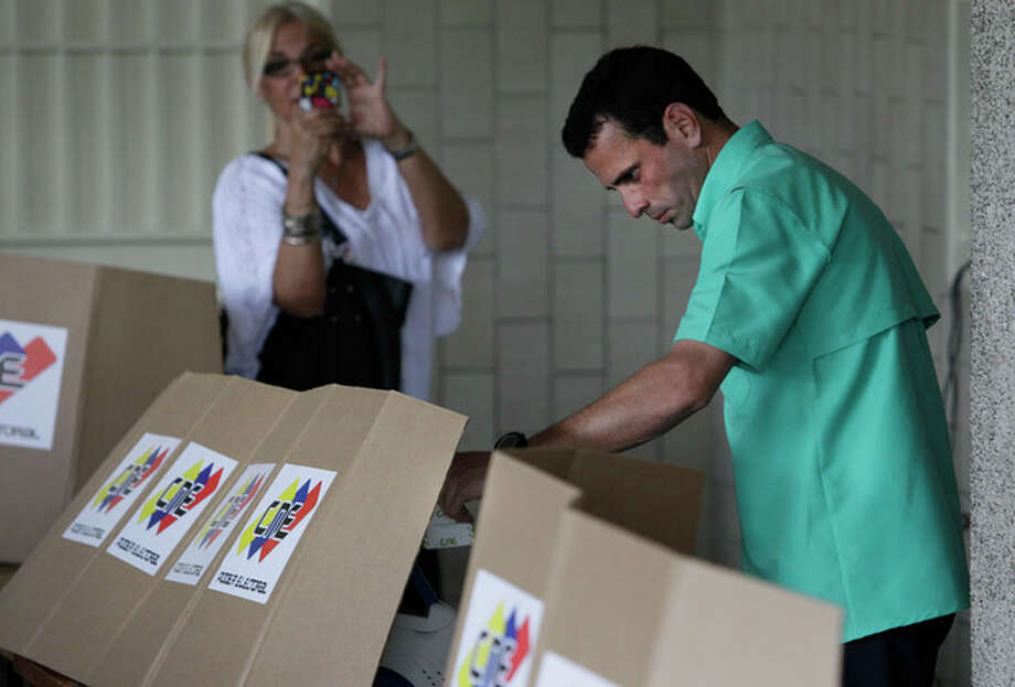 Henrique Capriles, the front-runner among five opposition presidential contenders, marks his ballot at a polling station in Caracas, Venezuela, Sunday Feb. 12, 2012. Venezuelans lined up to vote Sunday in the country's first-ever opposition presidential primary, choosing a single challenger they hope will have what it takes to defeat President Hugo Chavez in October, after 13 years in office. (AP Photo/Ariana Cubillos) / AP