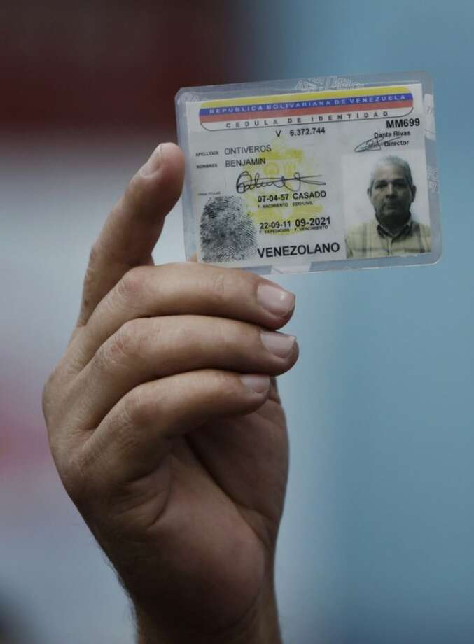 A voter holds up an identification card at a polling station during the opposition primary election in Caracas, Venezuela, Sunday Feb. 12, 2012. Citizens head to the polls Sunday in Venezuela's first-ever opposition primary to choose a candidate that will challenge President Hugo Chavez in October. (AP Photo/Ariana Cubillos)