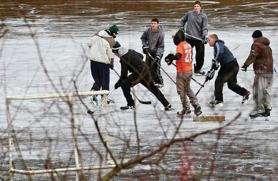 Hour photo / Erik TrautmannNorwalk high school alumni play hockey at Woods Pond Friday afternoon. Below, Norwalk resident Gote Snellman plays hockey. Then, on Saturday more folks ventured out. / (C)2012, The Hour Newspapers, all rights reserved