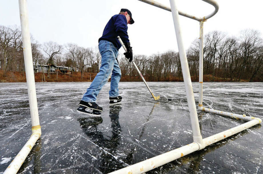 Norwalk Resident Gote Snellman plays hockey at Woods Pond Friday afternoon.Hour photo / Erik Trautmann / (C)2012, The Hour Newspapers, all rights reserved