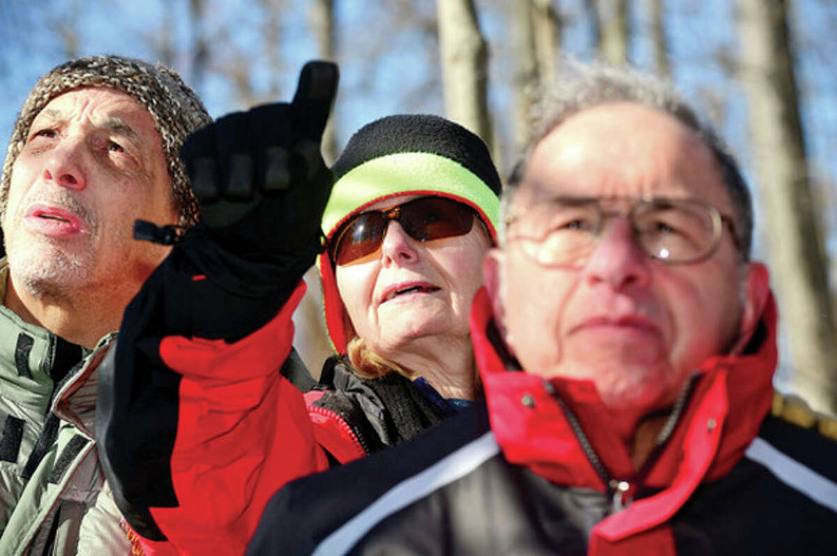"""Paul Cantor, Yvonne Lopaur and Dave Davidson look for wildlife while Master Conservationist for ther CT DEP Division of Wildlife, Larry Flynn, leads the Friends of Oak Hills Park """"Winter Walk in the Woods"""" Saturday morning viewing the woodland area of the park and talking about the wildlife that live there. Hour photo / Erik Trautmann"""