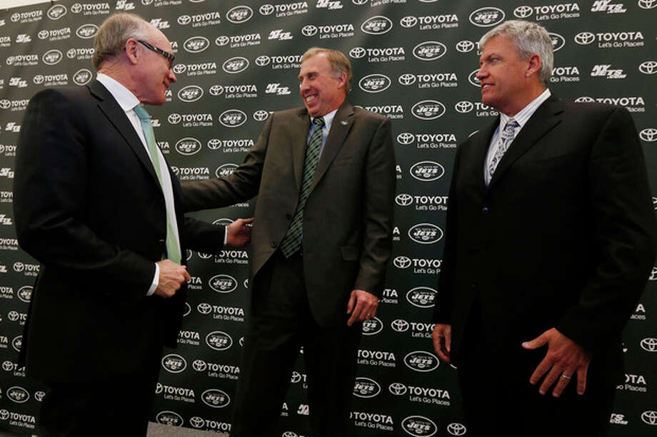 John Idzik, center, reacts while standing next to New York Jets owner Woody Johnson, left, and head coach Rex Ryan during an NFL football news conference introducing Idzik as the team's new general manager, Thursday, Jan. 24, 2013, in Florham Park , N.J. (AP Photo/Julio Cortez) / AP