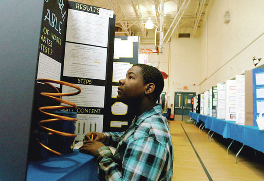 Pounus Middle School 7th grader evaluates finalists in the Norwalk Public Schools District Wide Science Fair at Ponus Ridge Middle School Wednesday as part of his class lesson. Hour photo / Erik Trautmann / (C)2011, The Hour Newspapers, all rights reserved