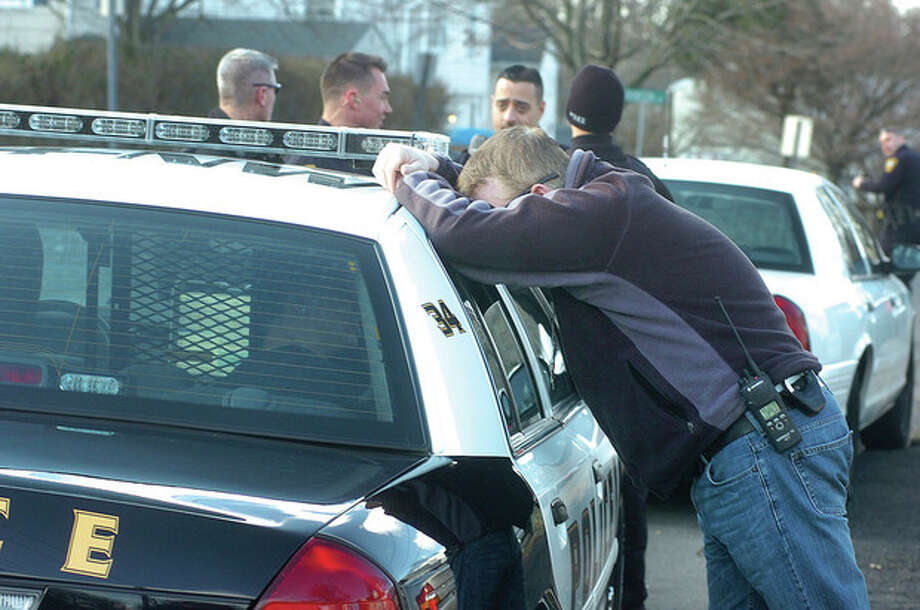 Hour photo/ Alex von Kleydorff Above, Norwalk Police talk with a person of interest in the back of a squad car on Grandview Avenue on Wednesday. Below, a machine gun confiscated during the investigation. / © 2012 The Hour Newspapers