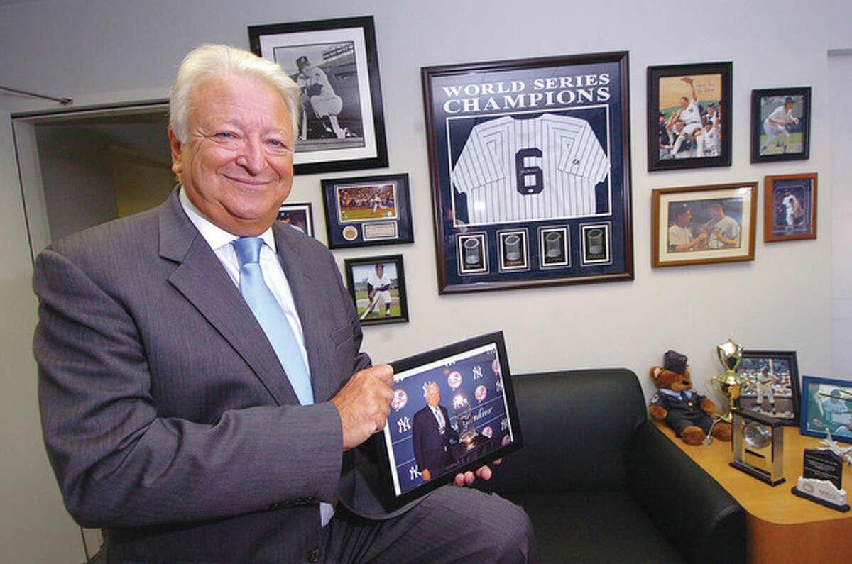 Photo/Alex von Kleydorff. Yankee fan Norwalk Mayor Richard Moccia holds a photo of himself with the Yankees World Series trophy.