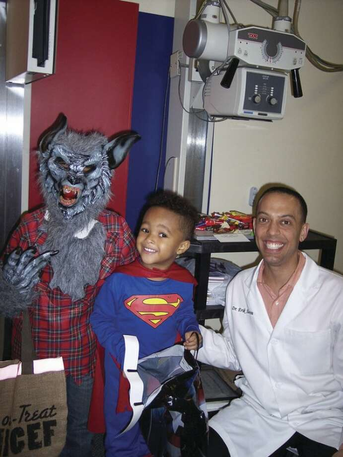 Contributed photo Elijah Canty, 3, and his brother, Nyreek Soto, 6, pose in their costumes on Halloween, Oct. 31, with Norwalk chiropractor Dr. Erik Slovin, Rotarian, after their treats were X-rayed for any possible foreign objects. With candies cleared, the boys could enjoy their just rewards.
