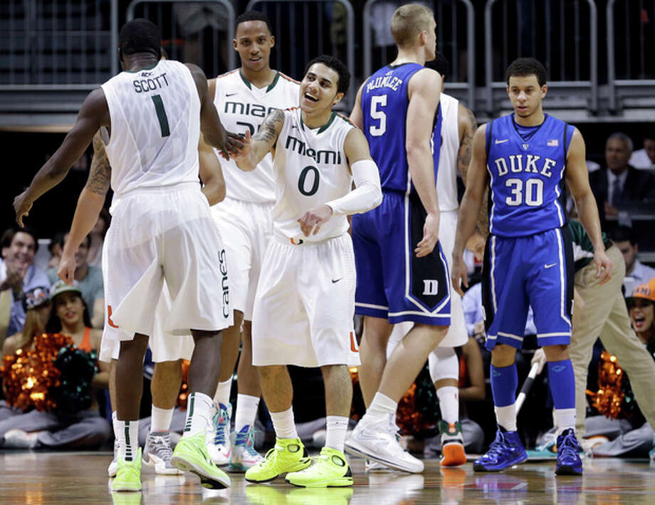 Miami's Shane Larkin (0) celebrates after Durand Scott (1) scored against Duke during the first half of an NCAA college basketball game in Coral Gables, Fla., Wednesday, Jan. 23, 2013. (AP Photo/Alan Diaz) / AP
