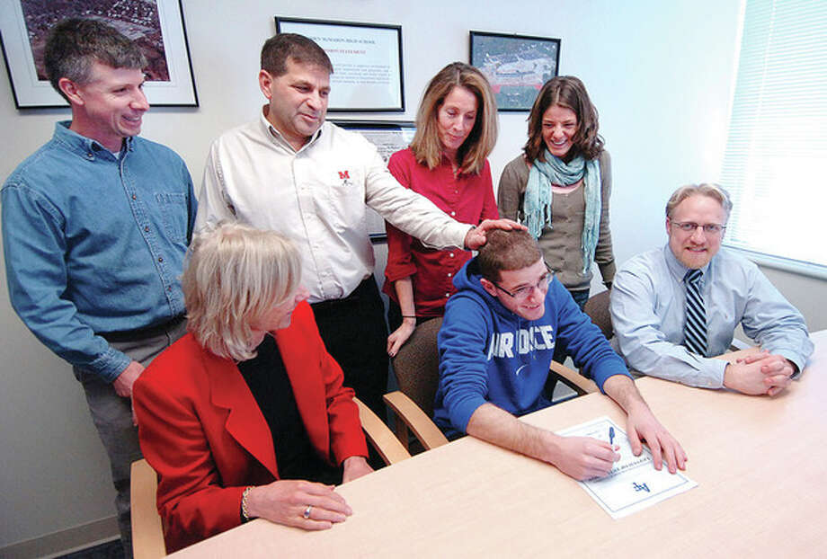 Hour photo/Alex von Kleydorff Chris Madaffari gets a pat on the head from his dad, Brien McMahon athletic director Joe Madaffari, after signing his National Letter of Intent to attend the Air Force Academy and run for the Falcons beginning in the fall. Flanking the McMahon track and cross country standout are school principal Suzanne Koroshetz and track coach Patrick Bradley. Standing behind the signee, from left, are coach Jeff Brentson, the athlete's parents, Joe and Eileen, and his sister Lauren. / © 2012 The Hour Newspapers