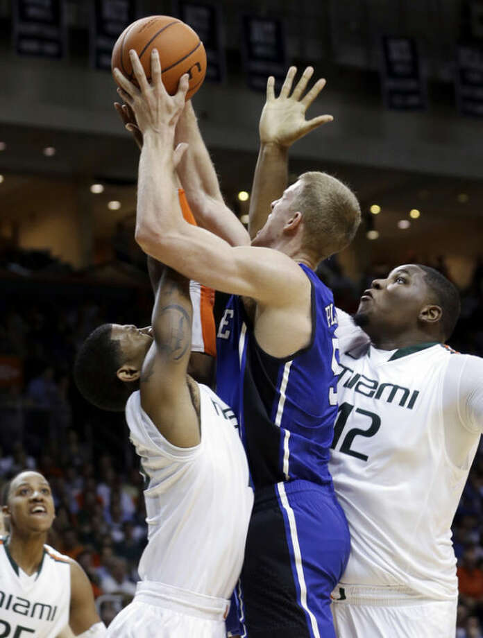 Miami's Reggie Johnson (42) and Miami's Rion Brown, left, apply pressure on Duke's Mason Plumlee (5) as he goes to the basket during the first half of an NCAA college basketball game in Coral Gables, Fla., Wednesday, Jan. 23, 2013. (AP Photo/Alan Diaz)