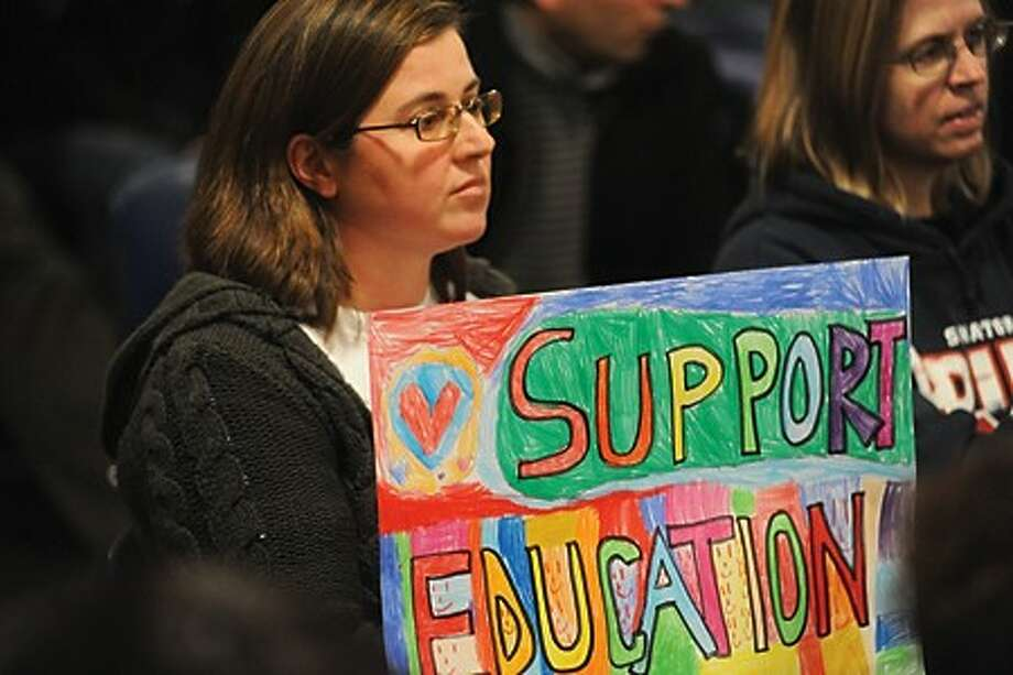 M.J. Chironna with a sign made by Norwalk 1st graders at the 2011-12 operating budget for Board of Estimate Taxation at Norwalk City Hall on Monday. hour photo/matthew ivnci