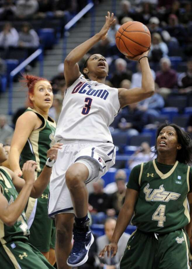 Connecticut's Tiffany Hayes, center, drives past South Florida's Caitlin Rowe, left, and Tiffany Conner (4) during the first half of an NCAA college basketball game in Hartford, Conn., on Saturday, Jan. 28, 2012. (AP Photo/Fred Beckham)