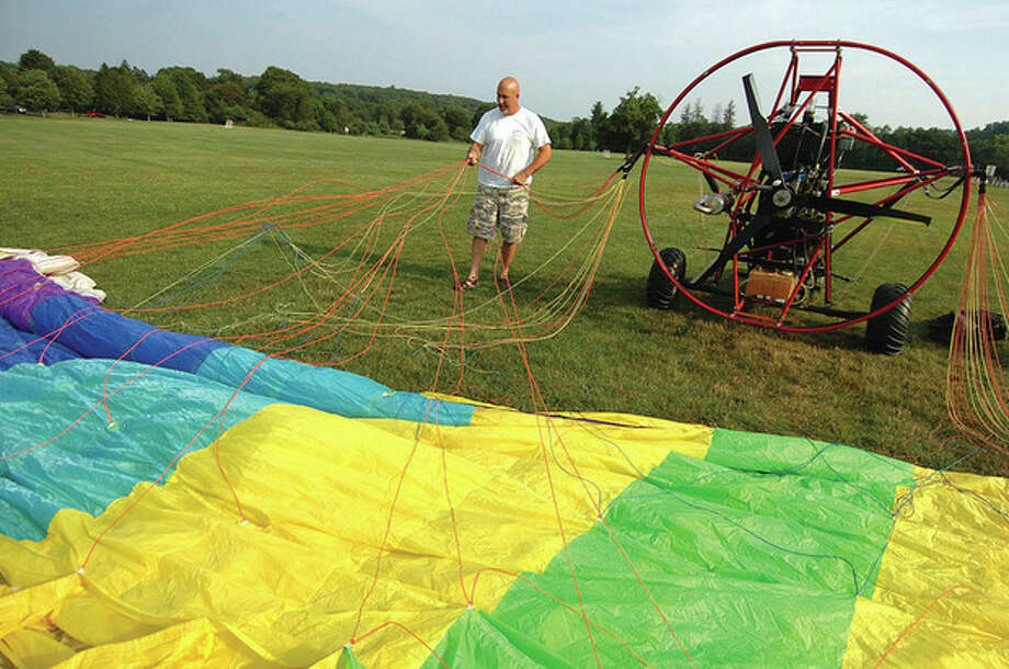 Hour Photo/Alex von Kleydorff. Rich Ruggles straightens the lines to the parachute before take off. / 2011 The Hour Newspapers