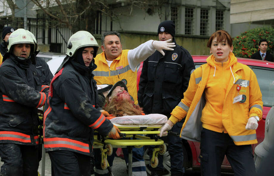 Medics carry an injured woman on a stretcher to an ambulance after a suspected suicide bomber detonated an explosive device at the entrance of the U.S. Embassy in the Turkish capital, Ankara, Turkey, Friday Feb. 1, 2013. The bomb appeared to have exploded inside the security checkpoint at the entrance of the visa section of the embassy. A police official said at least two people are dead. (AP Photo/Burhan Ozbilici) / AP