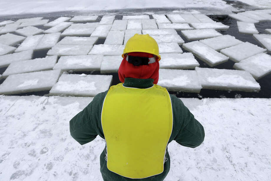 An inmate from the Moriah Shock Incarceration Correctional Facility cuts ice blocks from Lake Flower that will be used to construct the Saranac Lake Winter Carnival ice palace on Monday, Jan. 28, 2013, in Saranac Lake, N.Y. (AP Photo/Mike Groll) / AP