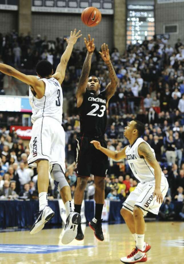 Cincinnati's Sean Kilpatrick (23) shoots the game-winning basket as UConn's Jeremy Lamb (3) and Shabazz Napier, right, defend with seconds left in Wednesday night's game at Gampel Pavilion. The visiting Bearcats took home a 70-67 victory. AP photo