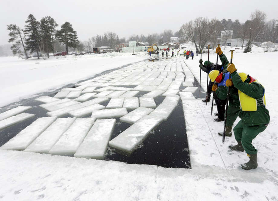 Inmates from the Moriah Shock Incarceration Correctional Facility, wearing green, work with volunteers breaking off ice blocks from Lake Flower that will be used to construct the Saranac Lake Winter Carnival ice palace on Monday, Jan. 28, 2013, in Saranac Lake, N.Y. (AP Photo/Mike Groll) / AP