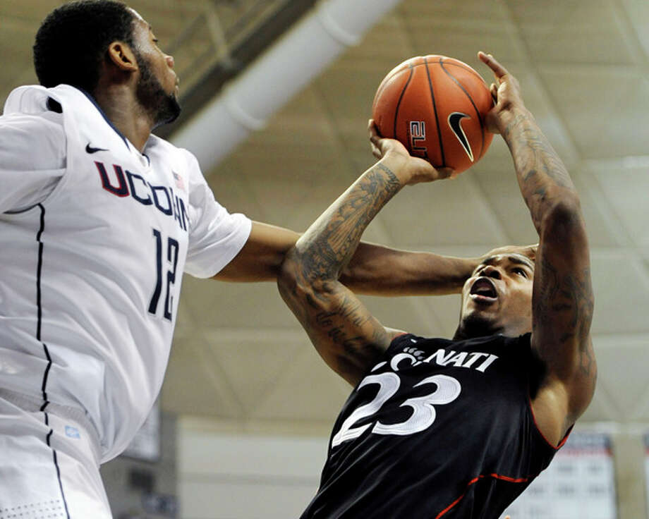 Cincinnati's Sean Kilpatrick (23) attempts a shot while fouled by Connecticut's Andre Drummond (12) in the first half of an NCAA college basketball game in Storrs, Conn., Wednesday, Jan. 18, 2012. (AP Photo/Jessica Hill) / AP2012
