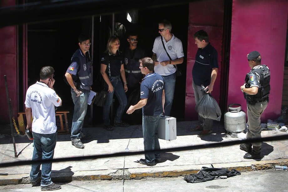 Police investigators work at the entrance of the Kiss nightclub where a fatal fire broke out in Santa Maria, Brazil, Monday, Jan. 28, 2013. A fast-moving fire roared through the crowded, windowless Kiss nightclub in this southern Brazilian city early Sunday, killing more than 230 people. Many of the victims were under 20 years old, including some minors. (AP Photo/Nabor Goulart) / AP