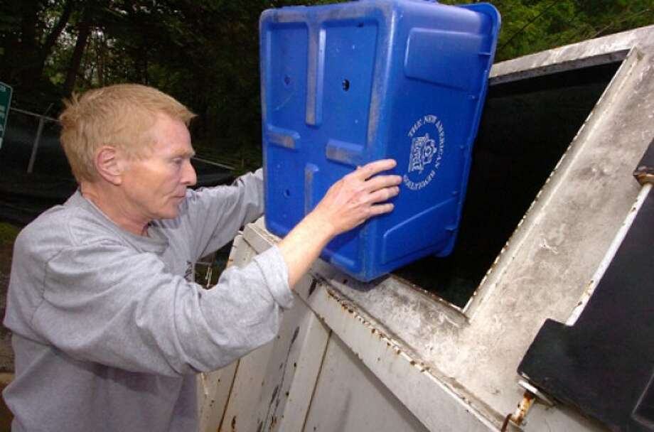 Photo by Alex von Kleydorff. Terence Kruska empties his recycle bin at the Town of Westport recycle center.