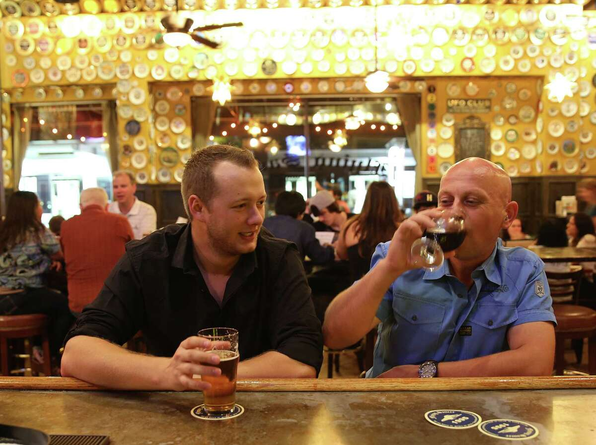 Andreas Willing, left, and Bertrand Meiss chat over beers at Flying Saucer on Saturday, Oct. 10, 2015, in Houston.