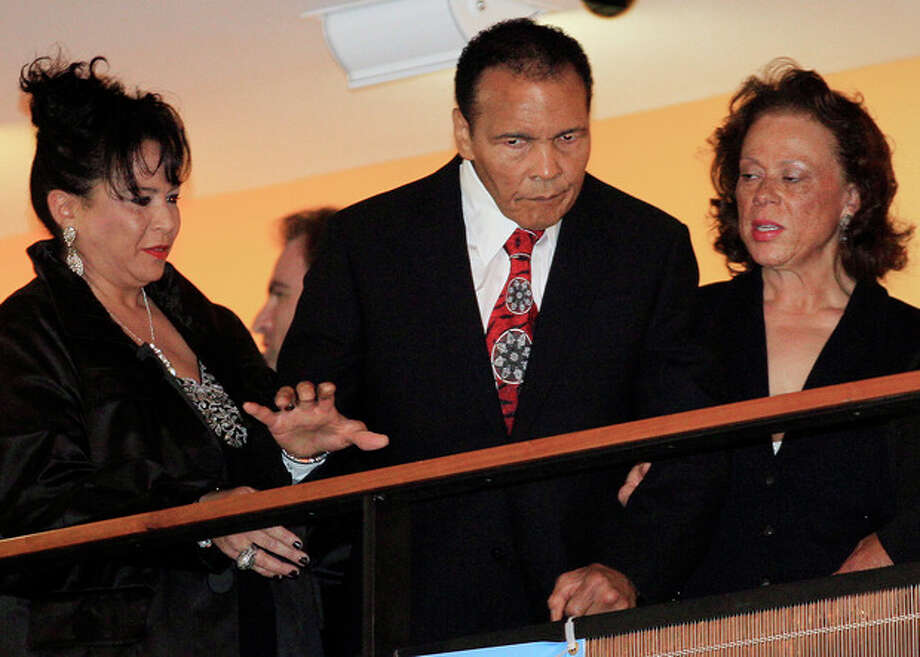 Boxing great Muhammad Ali is helped by his wife, Lonnie, right, and sister-in-law Marilyn Williams, left, as he looks down from a balcony at friends attending a celebration for his 70th birthday at the Muhammad Ali Center on Saturday, Jan. 14, 2012, in Louisville, Ky. Ali turns 70 Tuesday. (AP Photo/Mark Humphrey) / AP